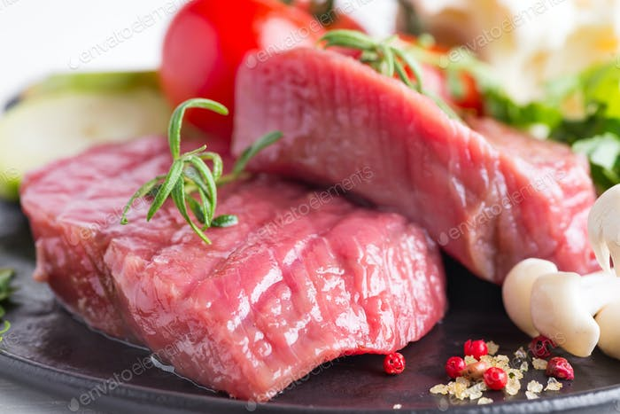 Raw beef steak on the bone with fresh vegetables in a pan on a marble background, top view