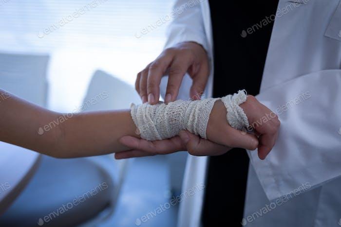 Nahaufnahme der gereiften gemischten Rasse Ärztin Untersuchung kaukasischen Mädchen Hand in Klinik im Krankenhaus