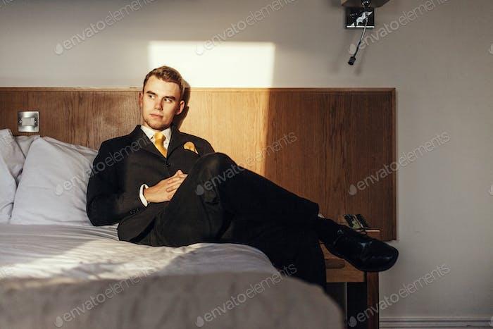 Продуманный хорошо одетый бизнесмен сидит на кровати в номере отеля