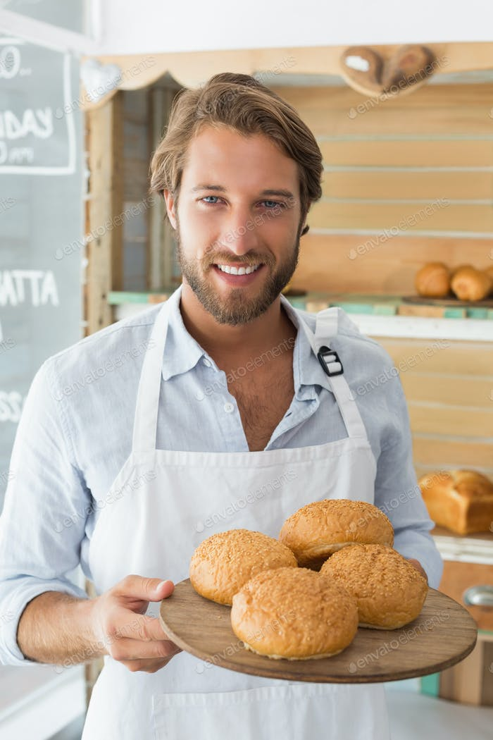 Handsome waiter holding tray of bread rolls at the coffee shop