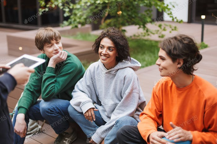 Smiling lady with dark curly hair sitting with her friends in courtyard of university