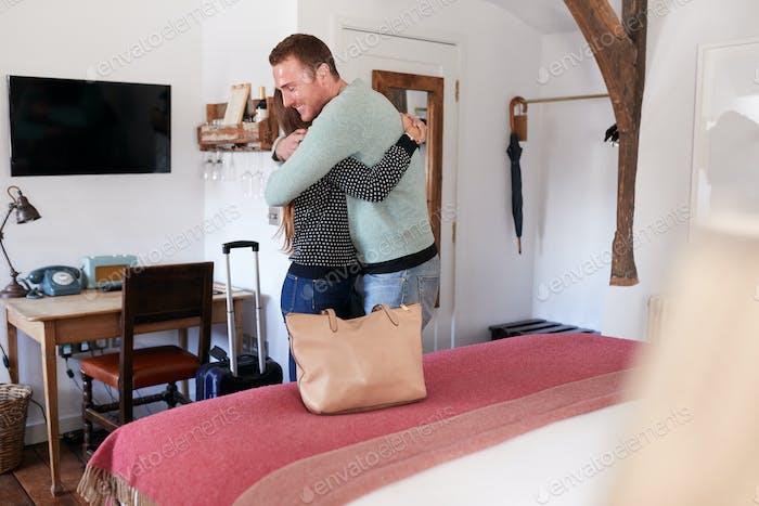 Couple Spending Romantic Weekend Away Hugging In Hotel Room