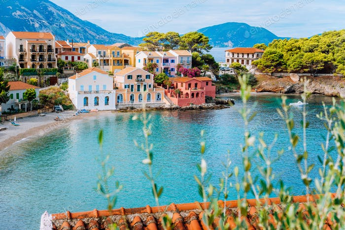 Assos village in Kefalonia, Greece. Turquiose bay, quite beach and colored traditional houses. Red