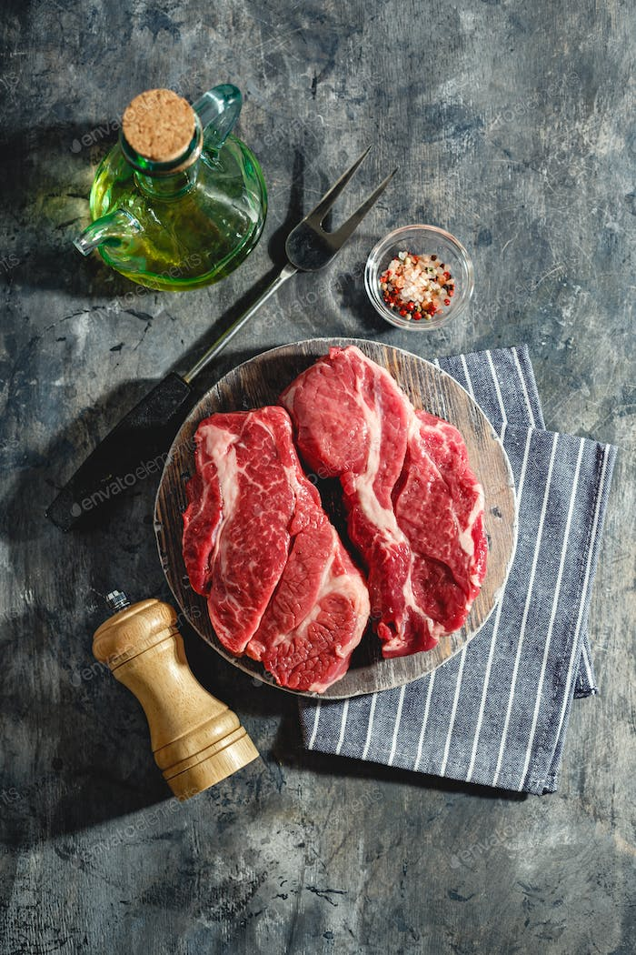 Raw beef steak on dark gray background