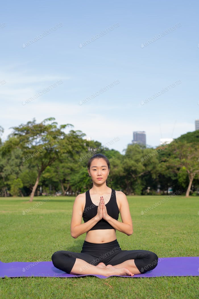 Woman Doing Meditation And Yoga In Park