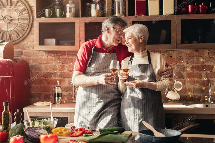 Cheerful senior couple clinking with wine glasses in kitchen