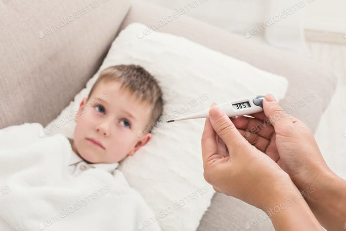 Mother measuring temperature of her ill son