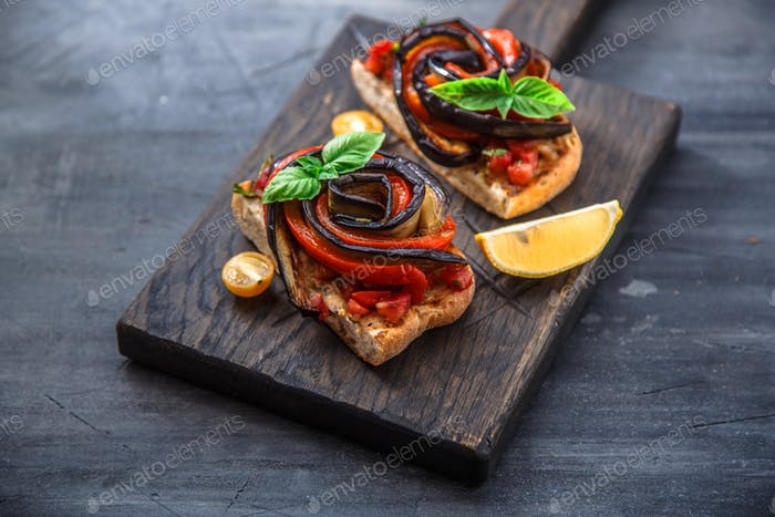Two bruschettas with baked aubergines and peppers on black background
