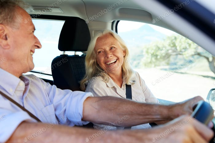 Senior white couple driving in their car, looking at each other, side view, close up