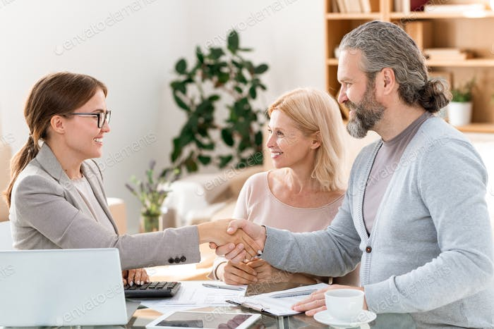 Happy young real estate agent congratulating mature clients on successful deal