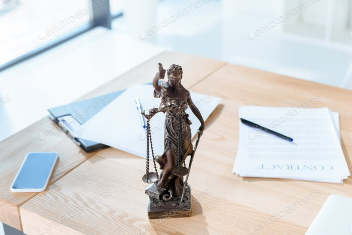 lawyer workplace with themis sculpture in modern office