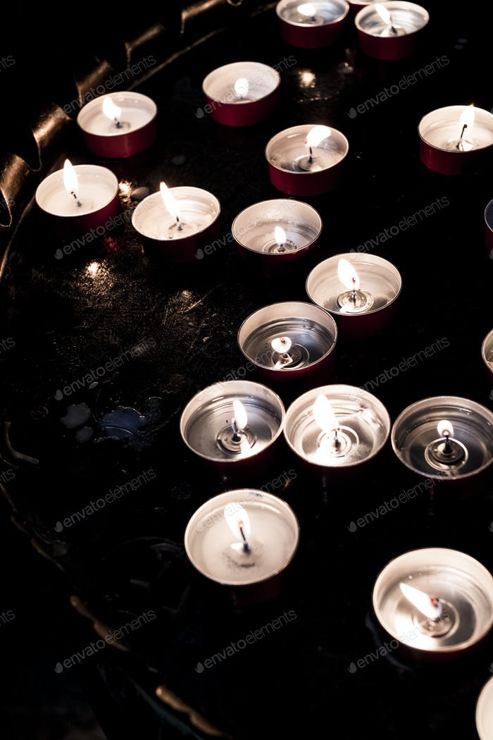 High angle close up of lit tea light candles on a tray in a church.