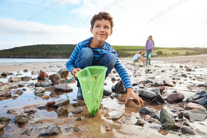 Children Looking In Rockpools On Winter Beach Vacation
