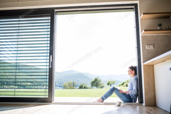 Side view of young woman with coffee sitting by patio door at home.