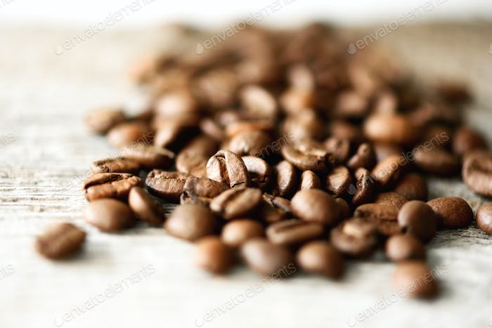 Coffee beans on light wooden background with copyspace for text. Coffee background, food frame
