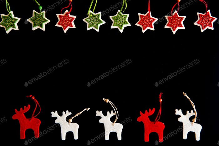 Felt rein deers iand snowflakes isolated on black. Christmas background with handmade ornaments
