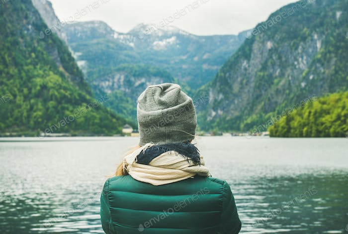 Female traveller standing at mountain lake coast in the Alps