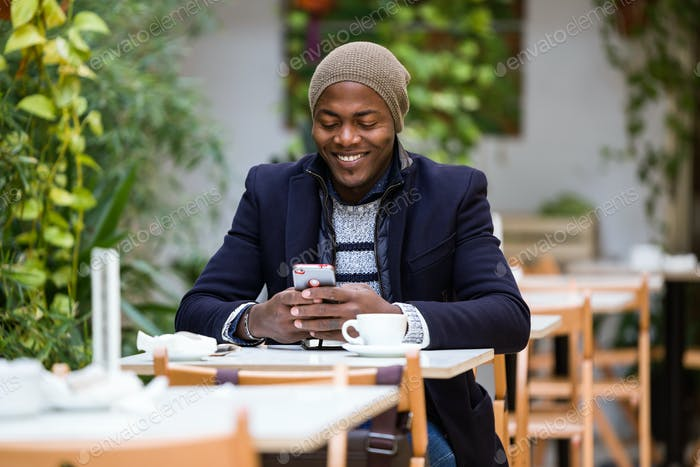 Handsome young man using his mobile phone in the cafe.