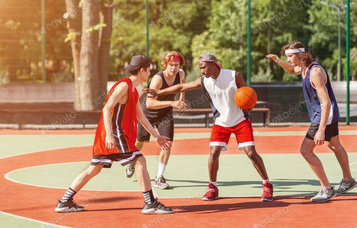Team of millennial sportsmen engaged in basketball game at outdoor court in summer