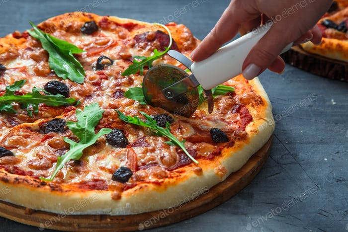 People Hands cutting homemade pizza with tomato, salumi, olives and arugula