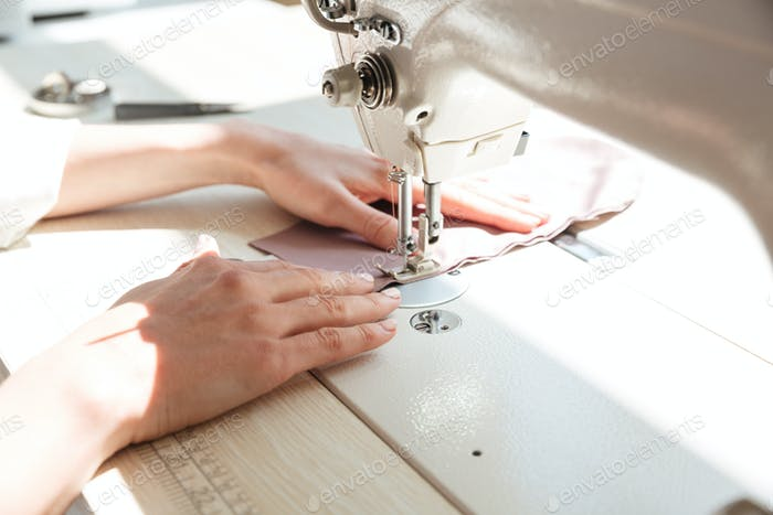 Close up of seamstress using sewing machine