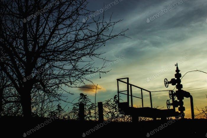 inusual silueta de perforación de gas, en el fondo de azul otoño puesta de sol cielo