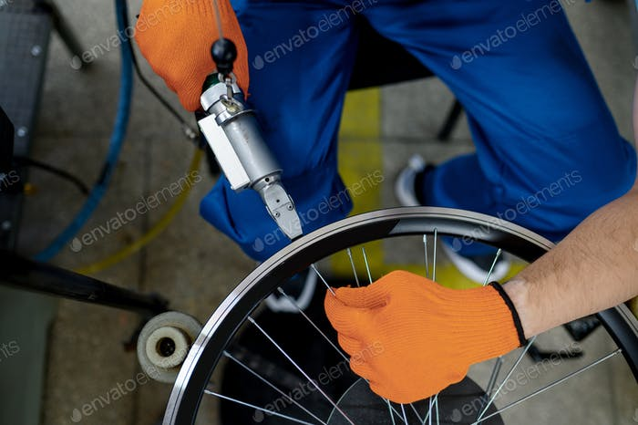 Worker with machine tool installs new bicycle rim