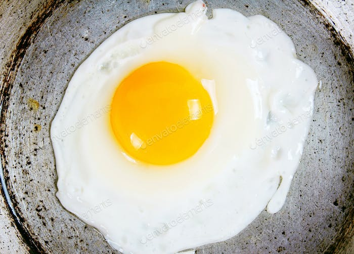 Egg fried on an old frying pan.