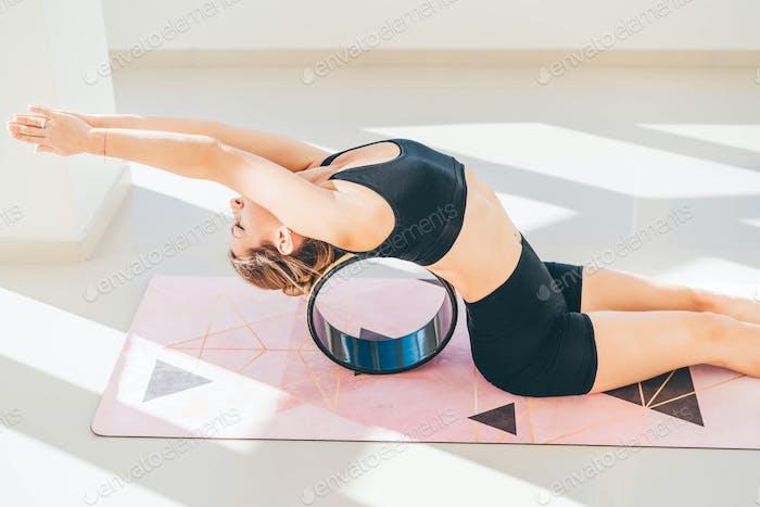 Sportliche Frau trainiert mit Yoga-Rad, um Wirbelsäulen- und Rückenflexibilität aufzubauen.