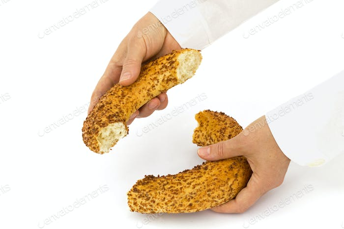 Baker holds a half from bagel, isolated on white background
