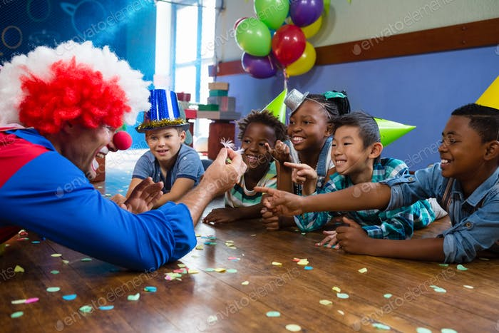 Clown showing feather to children