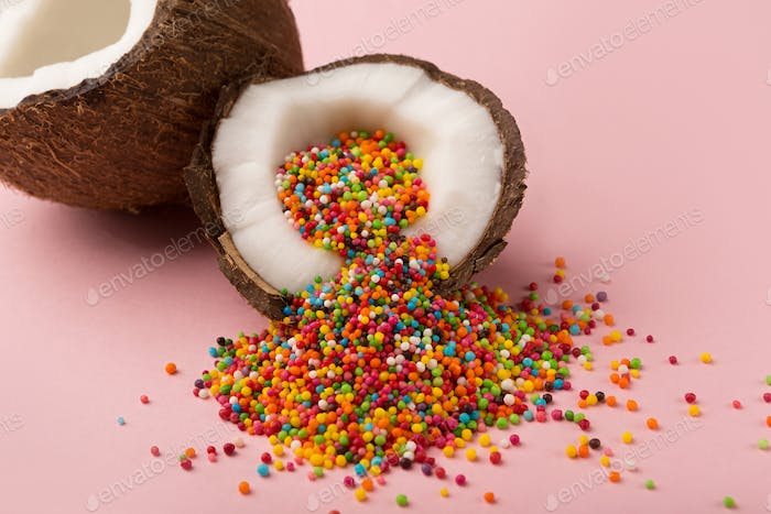 Coconut halves with sugar sprinkles inside at pink background