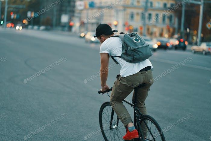 Junge moderne Mann Radfahren auf einem klassischen Fahrrad auf der Stadtstraße mit einem Rucksack