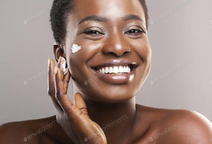 Porträt von Lächeln Schwarze Frau Anwendung Feuchtigkeitscreme auf Gesicht