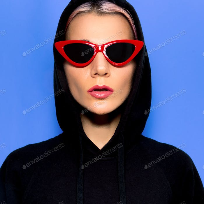 Model in fashion sunglasses and hoody. Urban Street Outfit Swag