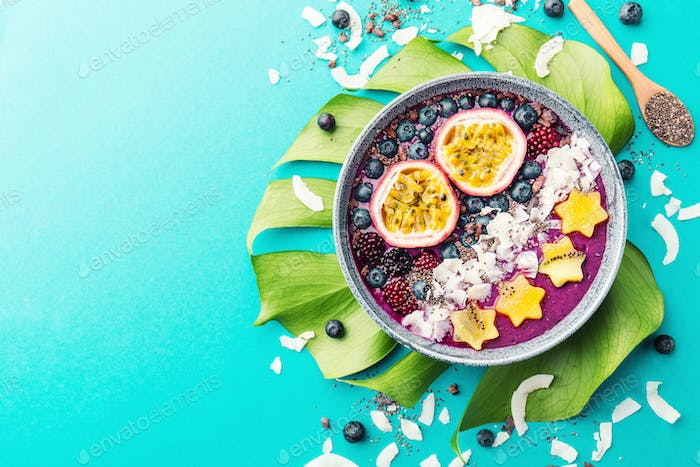 Smoothie acai bowl served in bowl on blue table