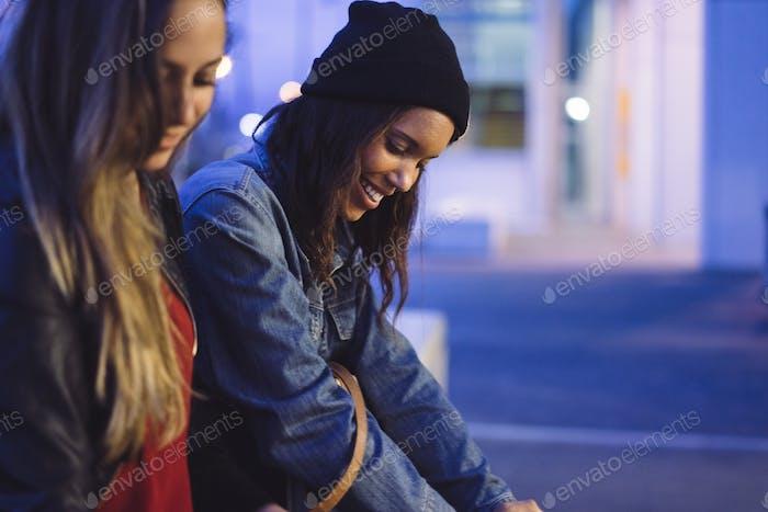 dos jóvenes amigas chateando y mirando a su teléfono móvil