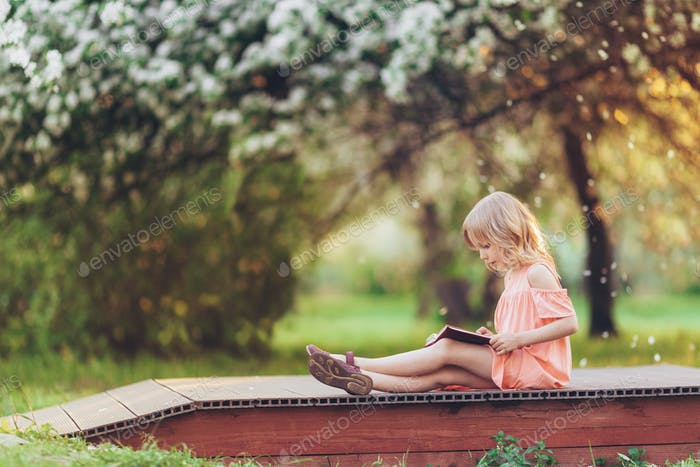 Little girl reading a book outdoors