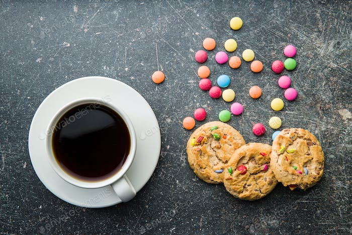 Sweet cookies with colorful candies and coffee mug.