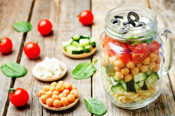 Pasta chickpeas cucumber tomatoes spinach goat cheese salad in a