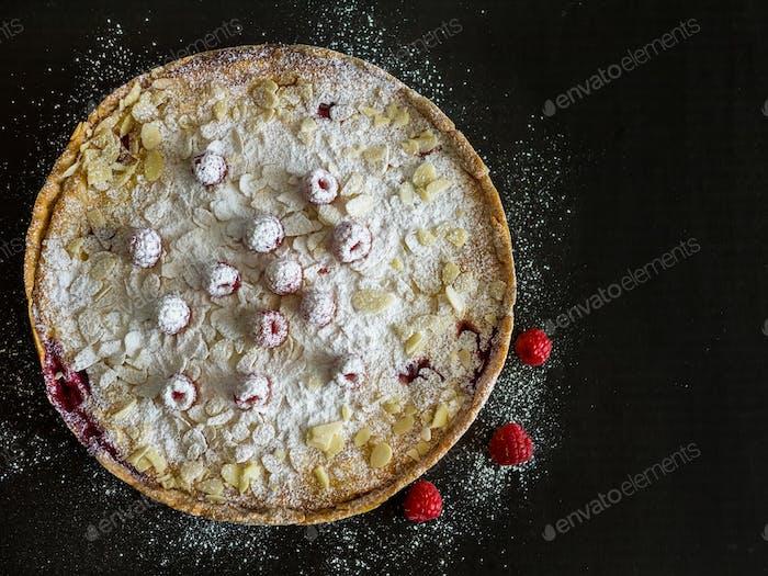 Raspberry and mascarpone pie on a black background