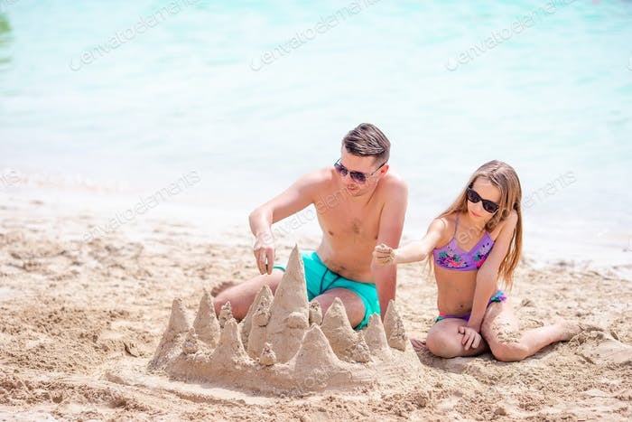 Father and kid making sand castle at tropical beach. Family playing with beach toys