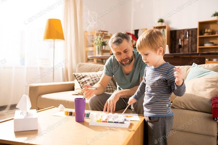 Отец учит сына рисовать