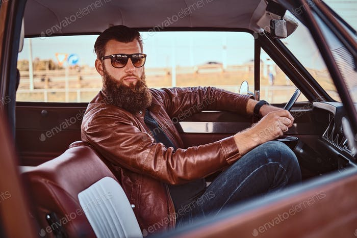 Бородатый мужчина в солнцезащитных очках, одетый в коричневую кожаную куртку за рулем ретро автомобиля.