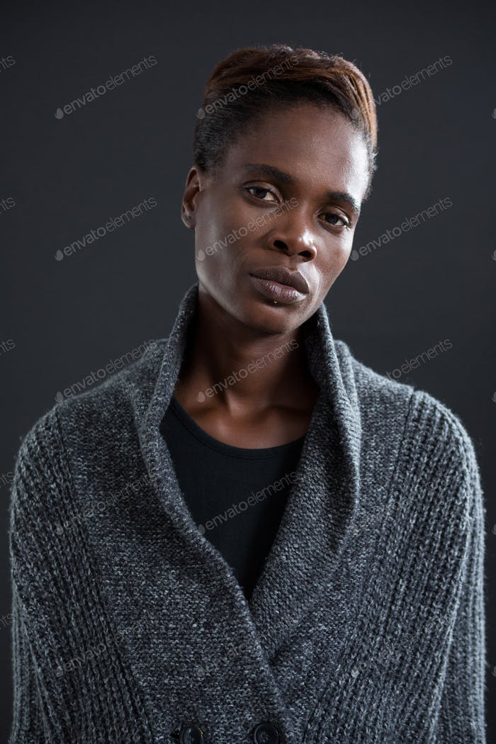 Androgynous man in sweater against grey background
