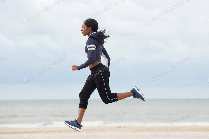 side portrait of sporty young black woman running by the beach