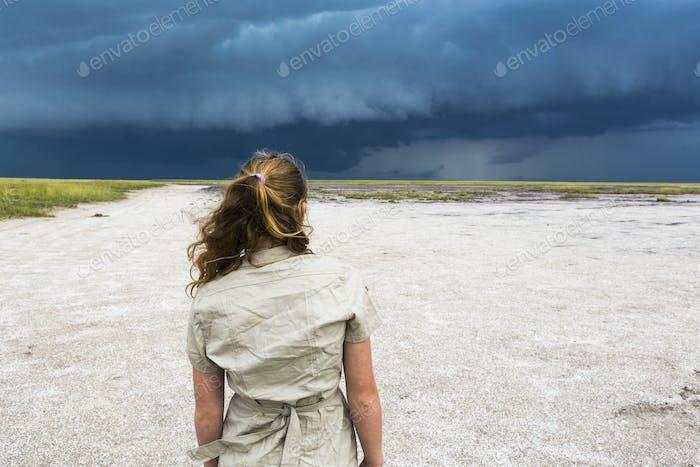 rear view of 13 year old girl looking at dramatic sky, Nxai Pan, Botswana
