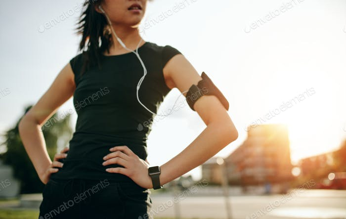 Young woman taking a break while on morning run