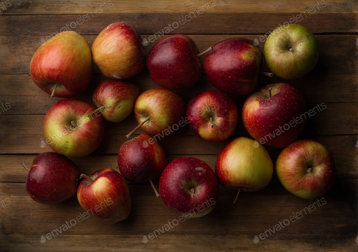 Organic small garden ripe apples on wooden plank