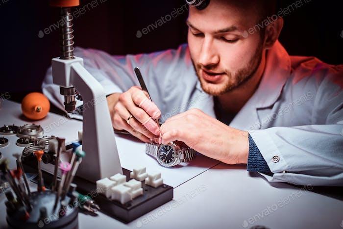 Expirienced Uhrmacher macht Gravur für Customers Uhr in seiner Werkstatt